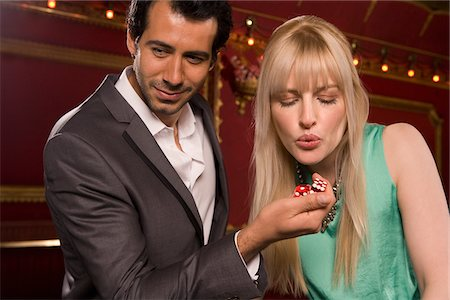 Girlfriend blowing on boyfriend's dice in casino Stock Photo - Premium Royalty-Free, Code: 635-03716332