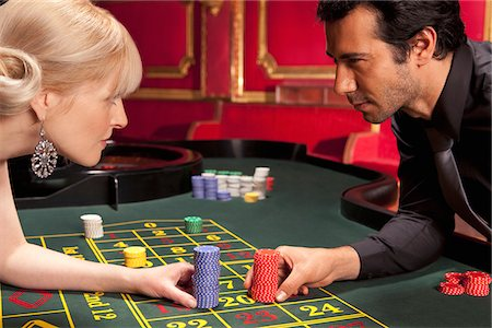 Man and woman placing bets at roulette table Stock Photo - Premium Royalty-Free, Code: 635-03716352