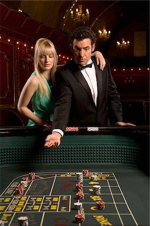 Girlfriend watching boyfriend throwing dice at craps table Stock Photo - Premium Royalty-Free, Code: 635-03716376