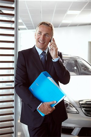 Salesman holding binder and talking on cell phone in automobile showroom Stock Photo - Premium Royalty-Free, Code: 635-03716414