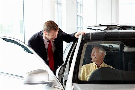 Salesman talking to man in new car in showroom Stock Photo - Premium Royalty-Free, Code: 635-03716412