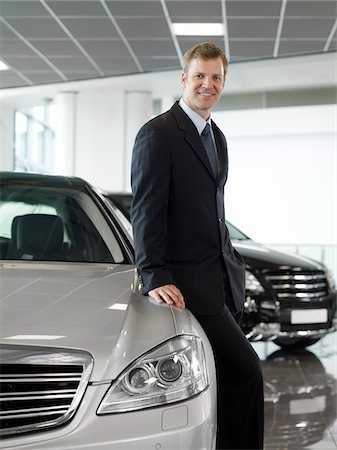 Salesman leaning on car in automobile showroom Stock Photo - Premium Royalty-Free, Code: 635-03716428