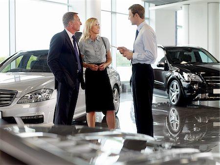Salesman talking to couple in automobile showroom Stock Photo - Premium Royalty-Free, Code: 635-03716423