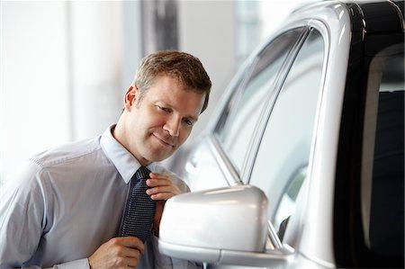 Salesman adjusting tie in side mirror of new car in showroom Stock Photo - Premium Royalty-Free, Code: 635-03716439