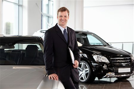 Salesman leaning on new car in showroom Stock Photo - Premium Royalty-Free, Code: 635-03716454