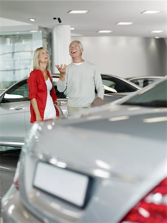 Couple tossing car key in automobile showroom Stock Photo - Premium Royalty-Free, Code: 635-03716466
