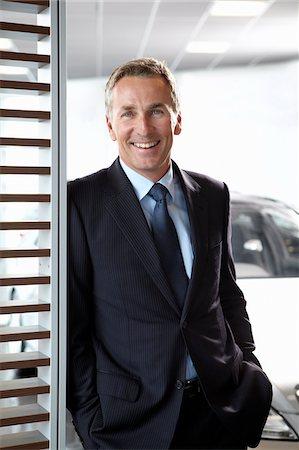 Salesman standing in automobile showroom Stock Photo - Premium Royalty-Free, Code: 635-03716504
