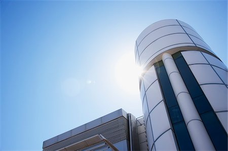 Sun shining over modern, circular office building Stock Photo - Premium Royalty-Free, Code: 635-03752132