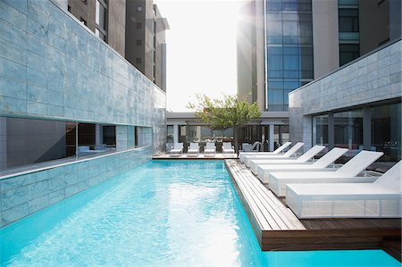 Modern lounge chairs next to swimming pool Stock Photo - Premium Royalty-Free, Code: 635-03752209