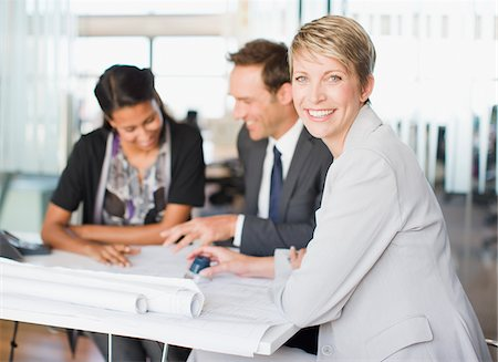 Business people looking at blueprints together Stock Photo - Premium Royalty-Free, Code: 635-03752298