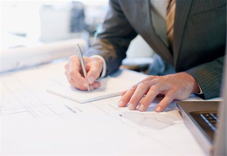 report - Businessman working on blueprints in office Stock Photo - Premium Royalty-Free, Code: 635-03752373