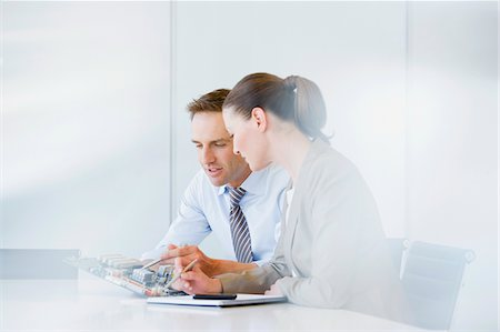 Business people looking at circuit board in office Stock Photo - Premium Royalty-Free, Code: 635-03752394