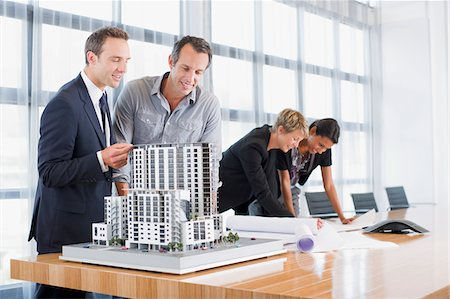 funny looking people - Business people looking at blueprints and model building Stock Photo - Premium Royalty-Free, Code: 635-03752393