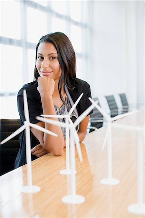 Businesswoman sitting in conference room with model turbines Stock Photo - Premium Royalty-Free, Code: 635-03752401