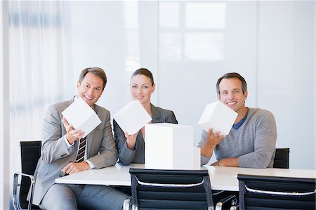 Business people holding white cubes in conference room Stock Photo - Premium Royalty-Free, Code: 635-03752412