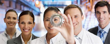 Business people looking at cog together Stock Photo - Premium Royalty-Free, Code: 635-03752424