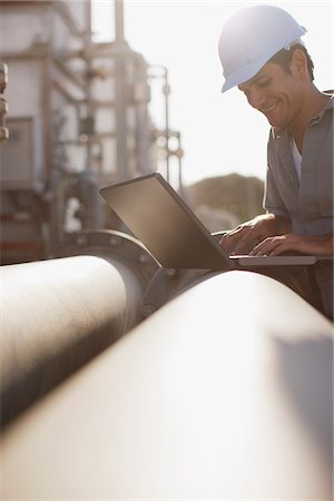 pipe (industry) - Worker in hard-hat working on laptop outdoors Stock Photo - Premium Royalty-Free, Code: 635-03752465