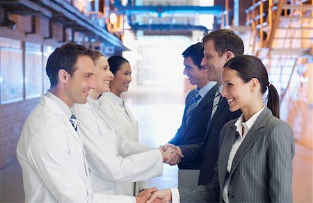 Business people shaking hands with scientists in factory Stock Photo - Premium Royalty-Free, Code: 635-03752466