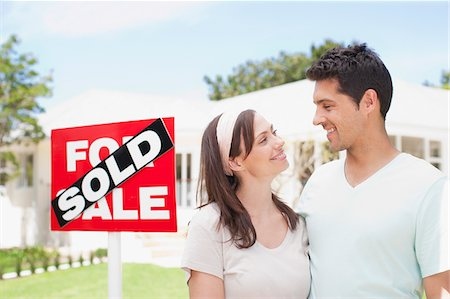 sold sign - Couple standing near sold sign of their new house Stock Photo - Premium Royalty-Free, Code: 635-03752507