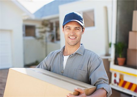 Smiling man carrying box from moving van Stock Photo - Premium Royalty-Free, Code: 635-03752523
