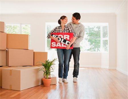sold sign - Couple holding sold sign for their new house Stock Photo - Premium Royalty-Free, Code: 635-03752533
