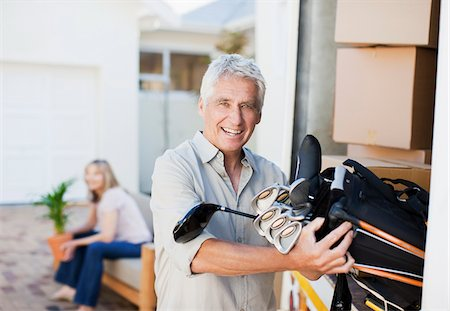 Man removing golf clubs from moving van Stock Photo - Premium Royalty-Free, Code: 635-03752546