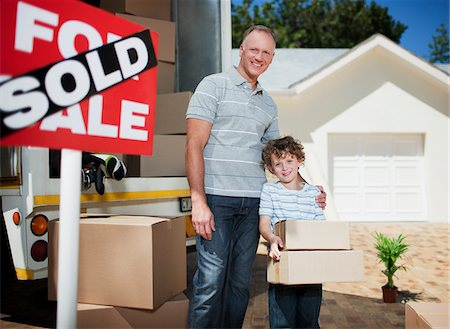 sold sign - Father and son with boxes standing near sold sign for their new house Stock Photo - Premium Royalty-Free, Code: 635-03752542