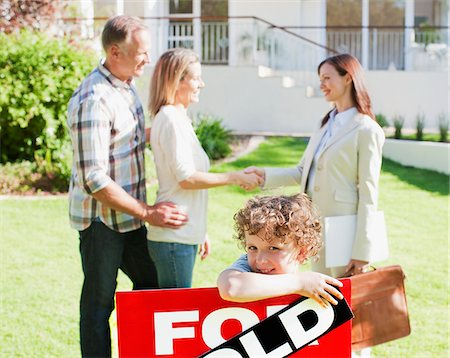 sold sign - Realtor congratulating family on buying new house Stock Photo - Premium Royalty-Free, Code: 635-03752557