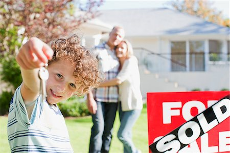 sold sign - Boy holding new house keys next to sold sign Stock Photo - Premium Royalty-Free, Code: 635-03752550