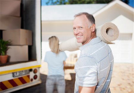 Couple carrying carpet from moving van Stock Photo - Premium Royalty-Free, Code: 635-03752563