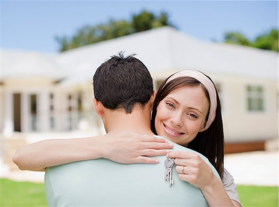 Couple hugging with keys to new house Stock Photo - Premium Royalty-Free, Image code: 635-03752575