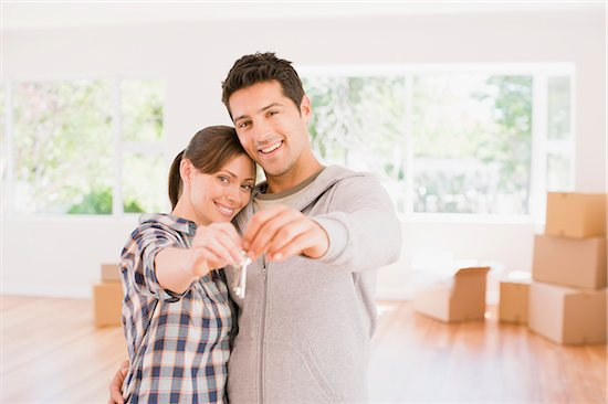 Couple holding the keys to their new house Stock Photo - Premium Royalty-Free, Image code: 635-03752577
