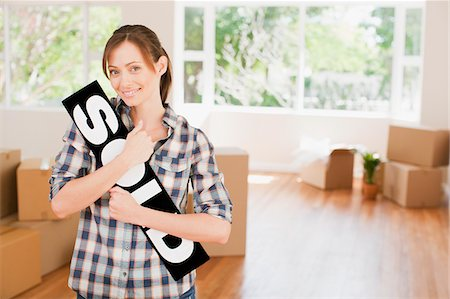 sold sign - Woman holding sold sign in her new house Stock Photo - Premium Royalty-Free, Code: 635-03752570