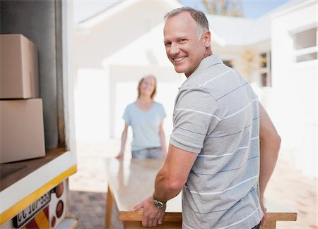 Couple carrying table from moving van Stock Photo - Premium Royalty-Free, Code: 635-03752589