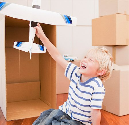 Grinning boy playing with model airplane in his new house Stock Photo - Premium Royalty-Free, Code: 635-03752598