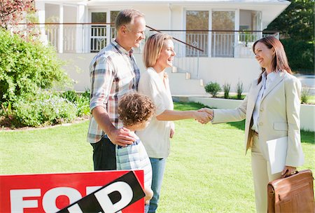 sold sign - Realtor congratulating family on buying their new house Stock Photo - Premium Royalty-Free, Code: 635-03752599