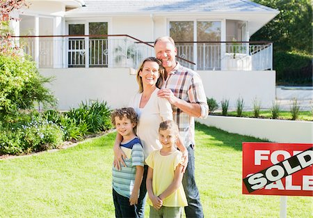 sold sign - Family standing in front yard of new house next to sold sign Stock Photo - Premium Royalty-Free, Code: 635-03752591