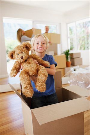 Boy playing with teddy bear in box in new house Stock Photo - Premium Royalty-Free, Code: 635-03752592