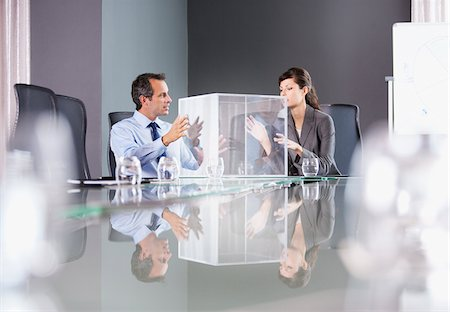 Business people looking at transparent cube in conference room Stock Photo - Premium Royalty-Free, Code: 635-03752619