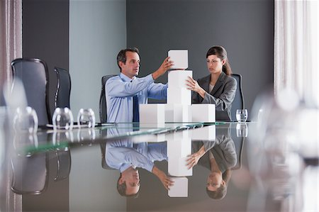 Business people stacking cubes in conference room Stock Photo - Premium Royalty-Free, Code: 635-03752610