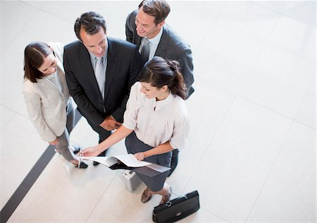 Business people reviewing report in office lobby Stock Photo - Premium Royalty-Free, Code: 635-03752622