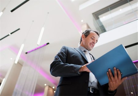report - Businessman reading report in lobby Stock Photo - Premium Royalty-Free, Code: 635-03752646