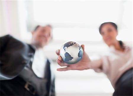Businesswoman holding small globe in office Stock Photo - Premium Royalty-Free, Code: 635-03752688