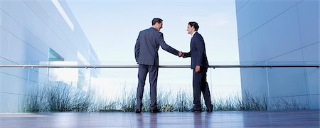 Businessmen shaking hands on balcony Stock Photo - Premium Royalty-Free, Code: 635-03752689