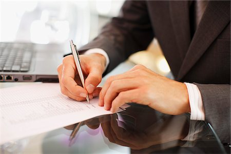 Businessman writing on paper at desk Stock Photo - Premium Royalty-Free, Code: 635-03752696