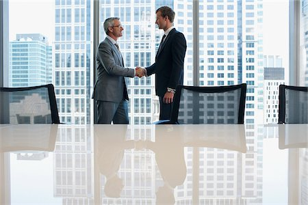 Businessmen shaking hands in conference room Stock Photo - Premium Royalty-Free, Code: 635-03752830