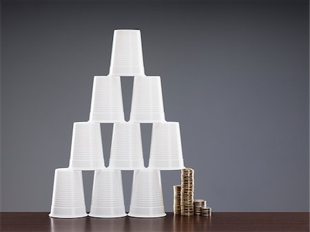 Coins holding up one side of cup pyramid Stock Photo - Premium Royalty-Free, Code: 635-03752889
