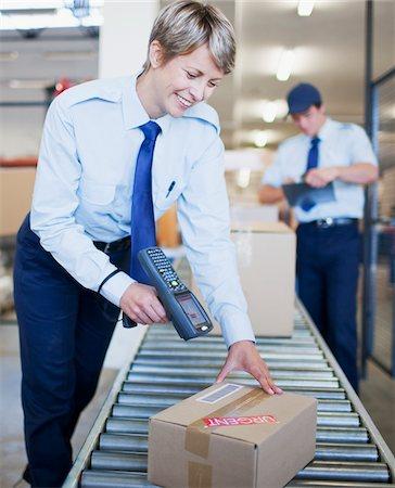Woman scanning box on conveyor belt Stock Photo - Premium Royalty-Free, Code: 635-03781316