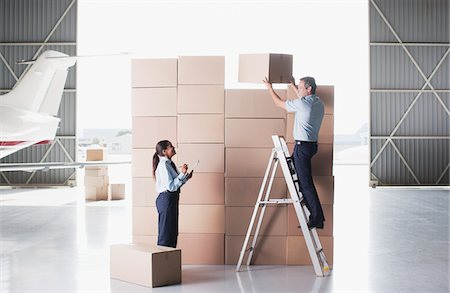 Workers stacking cardboard boxes in hangar Stock Photo - Premium Royalty-Free, Code: 635-03781320
