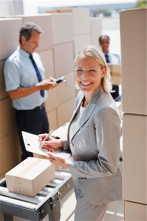 Supervisor holding clipboard in shipping area Stock Photo - Premium Royalty-Free, Code: 635-03781344